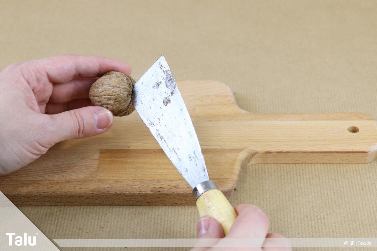 Walnüsse knacken in zwei Hälften, Spachtel zum Öffnen der Walnuss verwenden