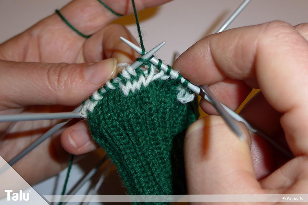 Gestrickte Socken, Norwegermuster, Nadelspiel mit Strickarbeit