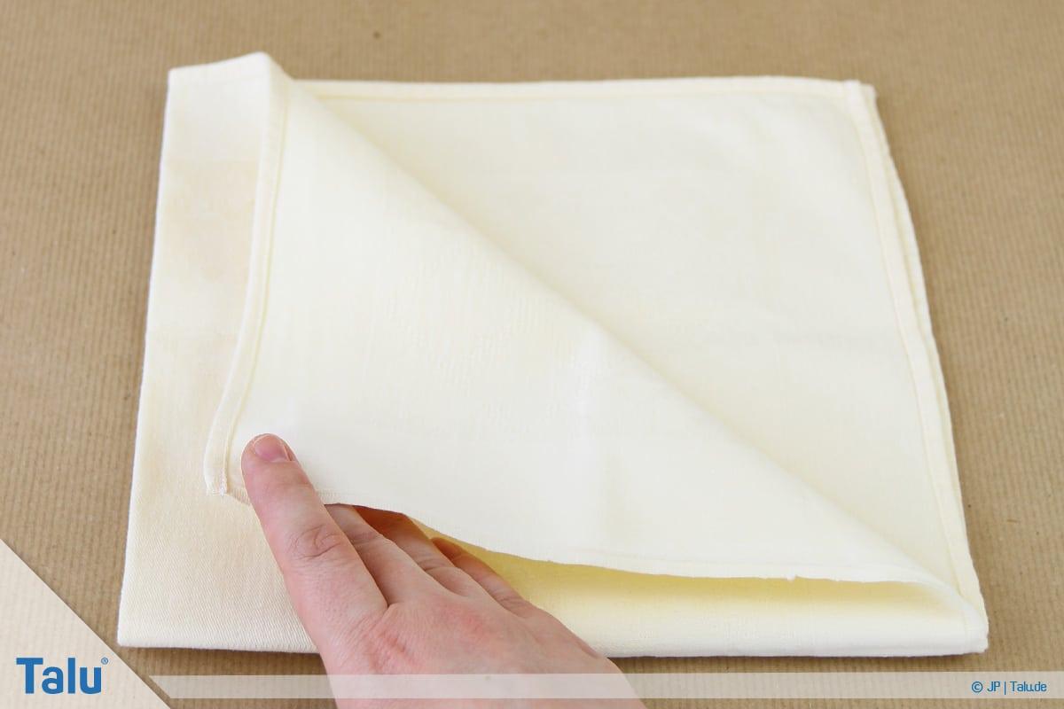 Stoffservietten falten, Bestecktasche, Teile der Serviette zur gegenüberliegenden Spitze falten