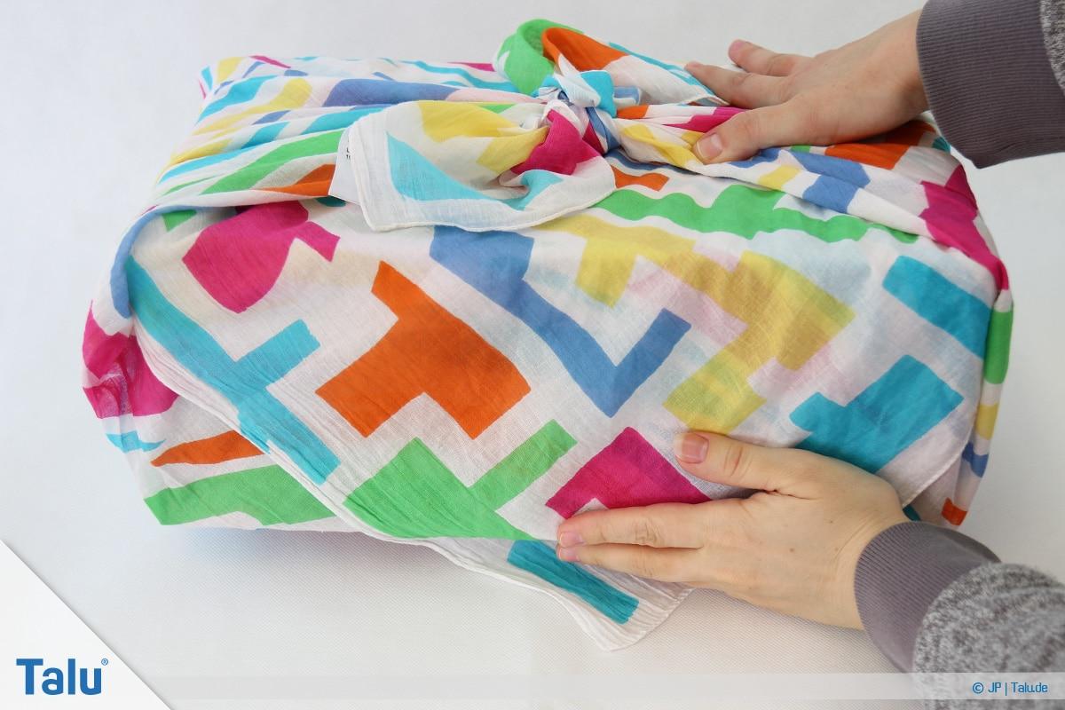 Furoshiki, Geschenke mit Stoff, Tüchern verpacken, Variante 1, vordere Ecke unter Geschenk geben