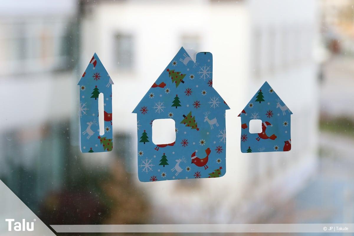 Basteln mit Papier an Weihnachten, Ideen, Fensterdeko aus Häusern an Glasscheibe anbringen